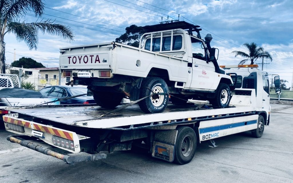 towing truck with a car on tray